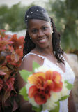 African american bride. An african american bride smiling holding out bouquet of flowers (focus on bride stock photos