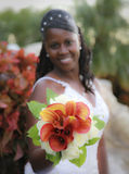 African american bride. An african american bride smiling holding out bouquet of flowers (focus on flowers stock photography
