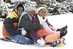 African American brothers and sister sliding on a sled. Royalty Free Stock Photography