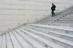 Hurrying to work. African-American business executive going down the stairs Stock Images