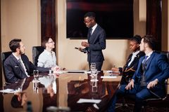 African American business man giving presentation to associates stock photography