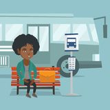 African woman waiting for a bus at the bus stop. African-american business woman with a briefcase waiting for a bus at the bus stop. Young smiling business Stock Image