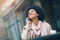 African american business woman talking on a cell phone. In front of an office building Royalty Free Stock Image