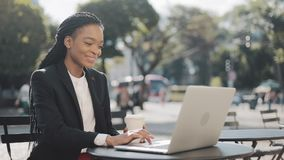 African american business woman using laptop, talking on the video conferencing or video chat. She sitting in cafe on. The summer terrace. Business stock footage
