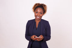 African American business woman using a smartphone - Black peopl. E Royalty Free Stock Images