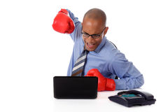 African American businessman, boxing gloves. Attractive young African American businessman in office, wearing boxing gloves. Ready to hit the laptop . Studio Stock Photography
