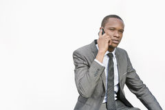 African American businessman conversing on cell phone over white background Royalty Free Stock Photography