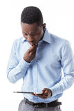 African American businessman with digital tablet. Frustrated African-American businessman saw the news in the tablet on white background Stock Photos
