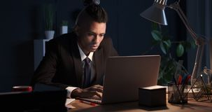 Businessman sleeping while working on laptop in night office stock footage