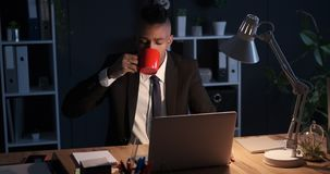 Businessman drinking coffee and working on laptop at night stock video footage