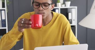 Businessman drinking coffee while working on laptop stock video