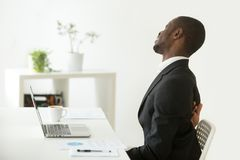 African-american businessman feeling sudden backache sitting on. African businessman feels strong backache sitting on uncomfortable office chair at work, black Stock Image