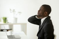 African-american businessman feels stiff neck joint pain after s. African american businessman feels neck pain sitting on uncomfortable office chair at work Stock Photos