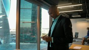 African American businessman in formal clothes chatting in messenger with smartphone. African American businessman in formal clothes chatting in messenger with stock footage