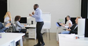 African american businessman funny dancing in modern coworking space cheering business people group on break stock footage