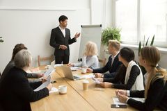 African-american businessman giving presentation explaining team. African businessman ceo boss in suit presenting corporate plan on flip chart at group meeting Stock Images