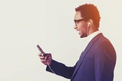 African American businessman in headphones is enjoying his playl Royalty Free Stock Photos