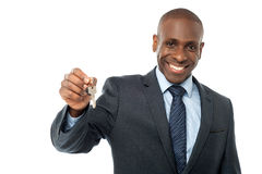 African American businessman holding a key. Real estate agent offering keys to the new home Royalty Free Stock Photo