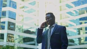 African American businessman holding mobile phone wearing blue suit stock video footage