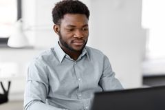 African american businessman with laptop at office. Business, people and technology concept - african american businessman with laptop working computer at office Royalty Free Stock Photography