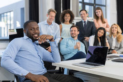 African American Businessman Leading Meeting In Creative Office, Boss Using Laptop Computer In Foreground Over Business stock photo