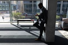 African-American businessman leaning against wall and using mobile phone in office royalty free stock photo