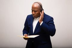 African American Businessman Listens Through Headset While Holding File royalty free stock photos