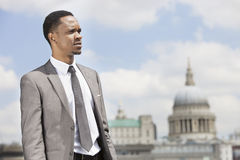 African American businessman looking away with St. Paul's Cathedral in the background Royalty Free Stock Images
