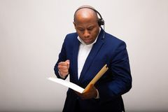 African American Businessman Looks Through File. With Deep Interest stock photography