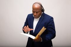 African American Businessman Looks Through File. Folder royalty free stock image