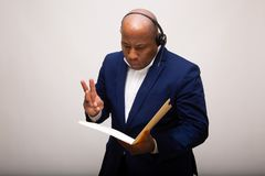 African American Businessman Looks Through File. Folder and Signals the Number Three stock photo