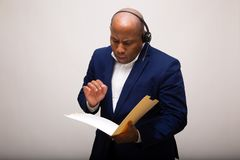 African American Businessman Looks Through File. Folder While Talking on the Phone royalty free stock photo