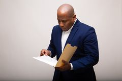 African American Businessman Looks Through Folder. Carefully stock photo