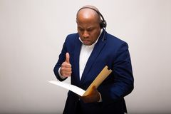 African American Businessman looks At Folder With Thumbs Up. African American Businessman looks At File Folder and Gives Thumb Up royalty free stock image