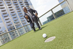 African American Businessman Playing Rooftop Golf Stock Images
