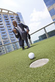 African American Businessman Playing Rooftop Golf stock photo