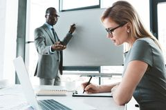 african american businessman pointing at whiteboard and looking at female colleague taking notes stock images