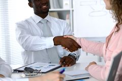 African american businessman shaking hands with female partner in office royalty free stock image