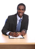 African American businessman signing document. Signing a documant in the office, a handsome young African American businessman wearing black suit and blue shirt Stock Image