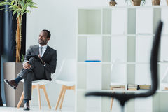 African american businessman sitting on chair in office and looking away Royalty Free Stock Photo