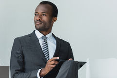 African american businessman sitting on chair in office and looking away Stock Photography