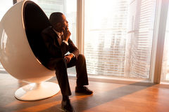 African-american businessman sitting in egg chair enjoying sunse Royalty Free Stock Photo