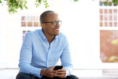 African american businessman sitting outside with mobile phone Stock Photo
