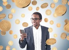 African American businessman, smartphone, bitcoins Stock Photo