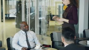 African American businessman smiling, drinking coffee and discussing startup with his Caucasian partner in classy cafe. Happy African American businessman stock footage