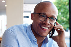 African american businessman smiling and talking on mobile phone Stock Photo