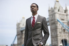 African American businessman standing against London Bridge Stock Photo