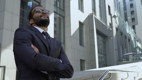African american businessman standing near office building, optimistic outlook