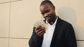 African american businessman in a suit counting money and showing money into the camera. He celebrating his successful. Win with a lot of dollars stock video