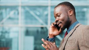 African American businessman in the sunglasses talking on the phone near the office building. Business, people. Technology, leisure and lifestyle concept stock video